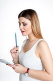 Young positive smiling student girl with notebook and pen planning her daily schedule wearing casual white t-shirt on white. Studi Royalty Free Stock Photos