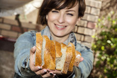 Young positive woman with fresh sliced bread. Young positive woman offering fresh sliced bread Royalty Free Stock Images