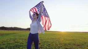 Young positive woman with an USA flag runs across a field at sunset slow mo. Young positive woman in glasses with an USA flag runs across a field at sunset slow stock video footage