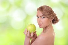 Positive woman with a green apple. Young positive woman with a green apple Stock Photos