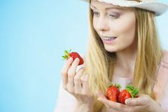 Young woman with fresh strawberries. Young positive woman holding in hands fresh strawberries fruits on blue. Healthy meal Stock Photo