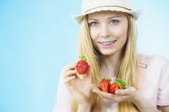 Young woman with fresh strawberries. Young positive woman holding in hands fresh strawberries fruits on blue. Healthy meal Stock Image