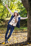 Young positive woman is leaning on the tree and relaxing by autu Royalty Free Stock Photography