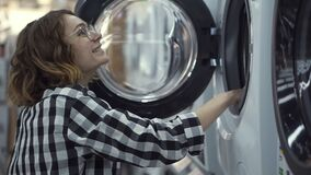 A young positive woman in a plaid shirt choosing washing machine in the shop of household appliances. Look inside to the. Open door and smiling. Side view. Slow stock video