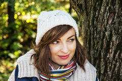 Young positive woman posing in autumn park, seasonal fashion Royalty Free Stock Photo