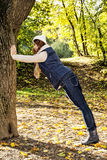 Young positive woman posing with tree and relaxing by autumn Royalty Free Stock Images