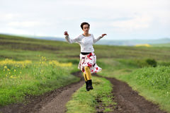 Young positive woman running on a countryside road. Freedom concept. Young woman running on a countryside road royalty free stock image
