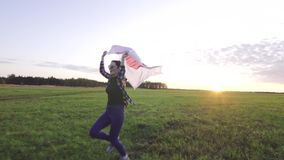 Young positive woman in a shirt runs across the field at sunset with the flag of Japan stock footage