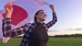 Young positive woman in a shirt runs across the field at sunset with the flag of Japan slow mo close up stock footage