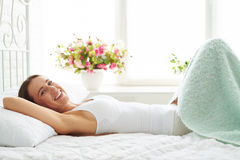 Young positive woman who's face shows enjoyment while lying on Royalty Free Stock Images