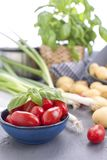 Young potatoes and cherry tomatoes and fresh onions. Ingredients for lunch. stock images