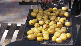 Young potatoes prepare on a grill. Hand using tongs for turning potatoes on the barbecue.  stock video