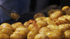 Young potatoes prepare on a grill. Hand using tongs for turning potatoes on the barbecue stock footage