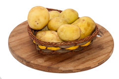 Young potatoes in a wicker basket Stock Photos
