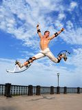 Young power jumper with stilts. Young power jumper on jumping stilts in park Royalty Free Stock Image