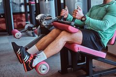 Strong active man is doing legs exercises on training apparatus in gym stock image