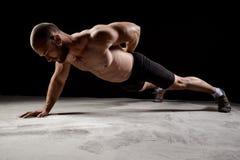 Young powerful sportsman training push ups over dark background. Young powerful sportsman training push ups on floor over dark background stock image