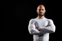 Young powerful sportsman in white clothing over black background. Royalty Free Stock Photos