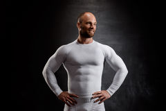 Young powerful sportsman in white clothing over black background. Royalty Free Stock Images