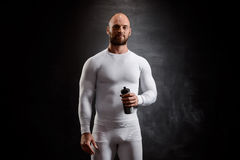 Young powerful sportsman in white clothing over black background. Royalty Free Stock Photo