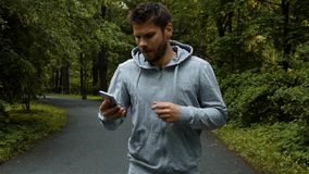 Young powerfull runner outside in autumn nature park with phone. Young powerfull handsome runner in gray hook wear, jogging outside in autumn nature park with stock video footage