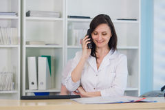 Young practitioner doctor working at the clinic reception desk, she is answering phone calls and scheduling appointments Stock Photo