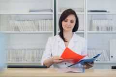 Young practitioner doctor working at the clinic reception desk, she is answering phone calls and scheduling appointments.  stock image
