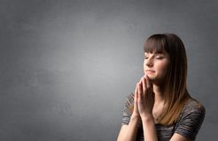 Young Praying girl. Young woman praying on a grey background Royalty Free Stock Photography