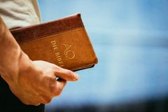 Christian preacher: Young man is holding the bible, praying royalty free stock photo