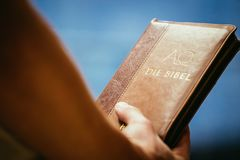 Christian preacher: Young man is holding the bible, praying stock photo