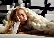 Young preety girl lying near new year christmas tree under big h. Andmade merino wool white blanket looking at the corner Royalty Free Stock Photos