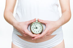 Young pregnant with alarm clock Stock Photography