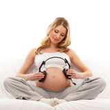 A young and pregnant blond holding headphones Royalty Free Stock Photos