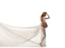 A young and pregnant blond woman in white silk Royalty Free Stock Photo