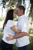 Young Pregnant couple. A young man kissing the nose of pregnant wife outside under a tree stock images