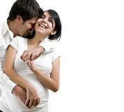 Young pregnant couple. Smiling over white background royalty free stock photography