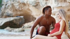 Young pregnant couple on a beautiful beach. Mixed ethnicity relationships