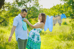 Young pregnant couple hang laundry Stock Photo