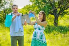 Young pregnant couple hang laundry Royalty Free Stock Images