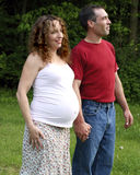 Young Pregnant Couple Holding Hands. An expectant mother and her husband hold hands stock photography