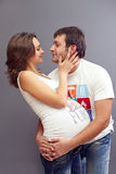 Young pregnant couple in love. On grey Stock Photography