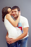 Young pregnant couple in love embracing. On grey Royalty Free Stock Photo