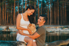 Young pregnant couple in love. On summer sunny evening, with dog royalty free stock photo