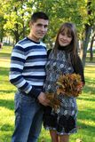 Young pregnant couple in park. Young pregnant couple with maple leaves in autumn park Stock Photography
