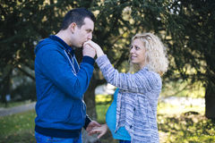 Young pregnant couple in the park. Pregnant couple in the park Royalty Free Stock Photo