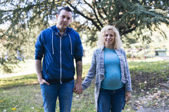 Young pregnant couple in the park. Young pregnant couple holding hands in the park Royalty Free Stock Photography