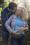 Young pregnant couple in the park. Young pregnant couple hugging in the park Royalty Free Stock Photo