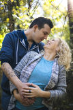 Young pregnant couple in the park. Young pregnant couple hugging in the park Royalty Free Stock Image