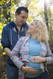 Young pregnant couple in the park. Young pregnant couple standing in the park Stock Photo