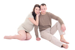 Young pregnant couple sitting isolated on white background Stock Images